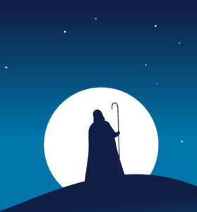 Guy in hooded cloak with a stick walking to a village in the night.